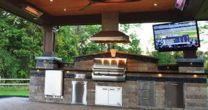 an outdoor kitchen and dining area as one of the landscaping tips